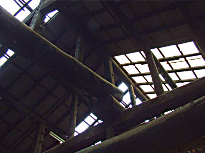 太い梁で組まれた米蔵の天井の写真