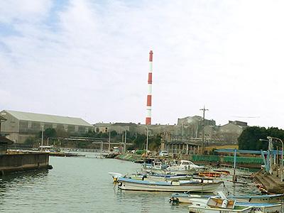 工場から伸びる朱と白の煙突の写真